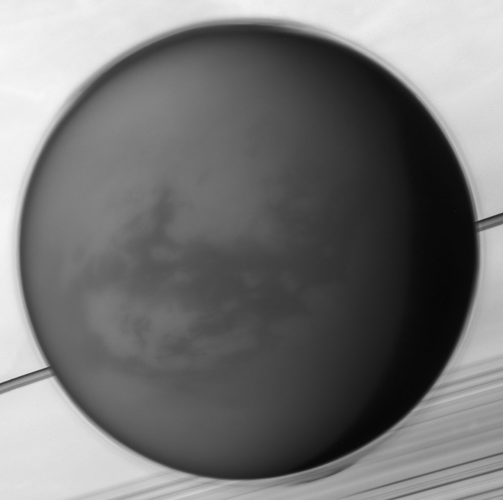 The detached haze layer that surrounds Titan is clearly visible against Saturn and its rings in the background, the haze growing more complex in its structure near the poles in this image from NASA's Cassini spacecraft.