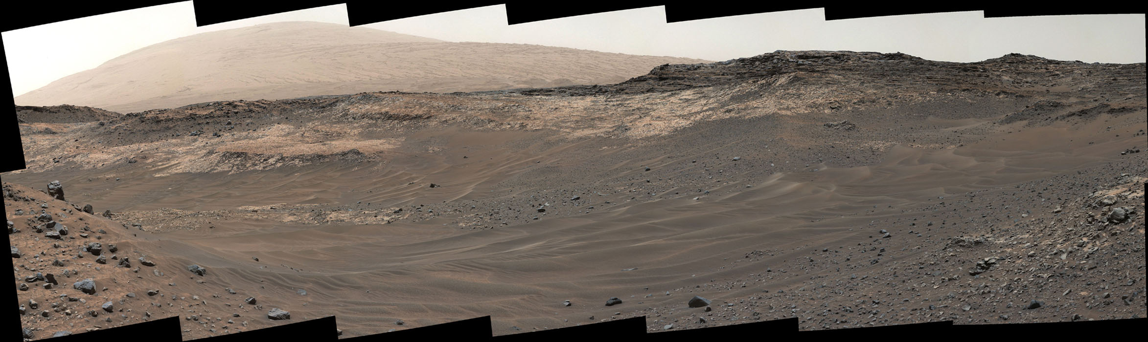 This view southeastward from Curiosity's Mast Camera (Mastcam) shows terrain judged difficult for traversing between the rover and an outcrop in the middle distance where a pale rock unit meets a darker rock unit above it.