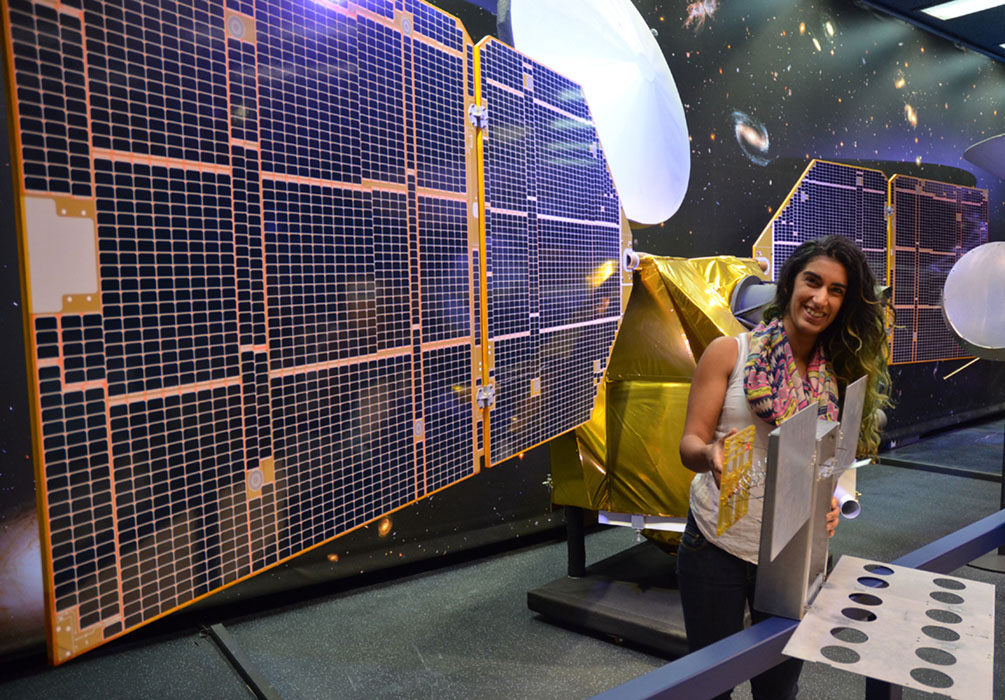 The full-scale mock-up of NASA's MarCO spacecraft held by Farah Alibay, a systems engineer for the project, is dwarfed by the one-half-scale model of NASA's Mars Reconnaissance Orbiter behind her.