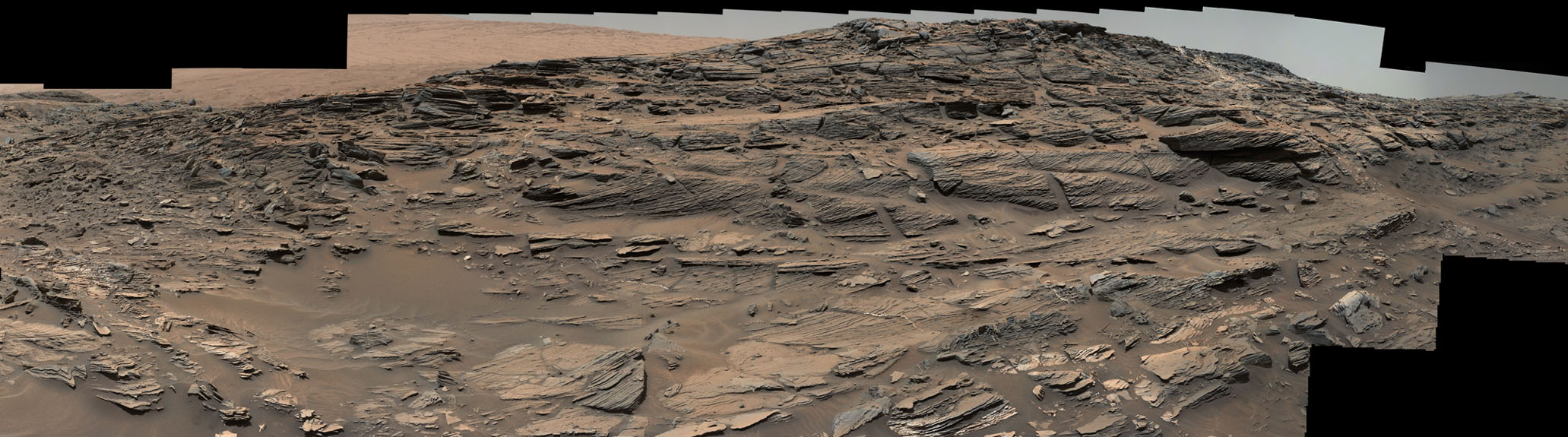 Large-scale crossbedding in the sandstone of this ridge on a lower slope of Mars' Mount Sharp is typical of windblown sand dunes that have petrified. NASA's Curiosity Mars rover used its Mastcam to capture this vista on Aug. 27, 2015.
