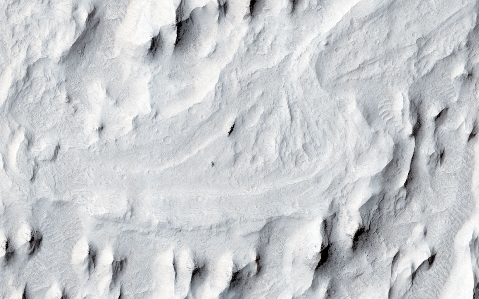 In this image from NASA's Mars Reconnaissance Orbiter spacecraft, an ancient sinuous meandering river system is surrounded by features called 'yardangs.' The yardangs are the ridge-like landforms that align approximately north-south.
