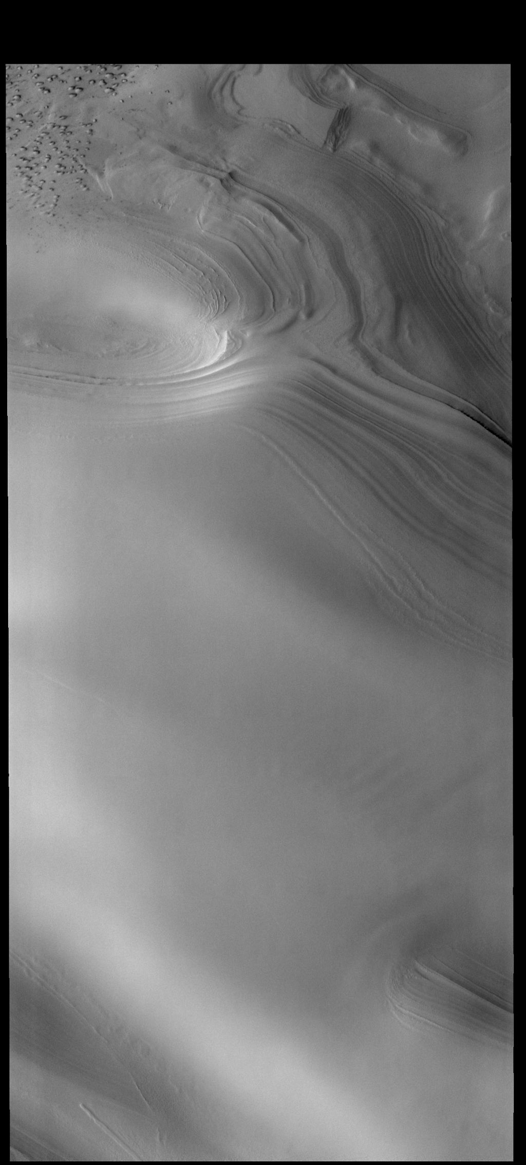 This image captured by NASA's 2001 Mars Odyssey spacecraft shows part of the margin of the north polar cap. Layering of the ice is visible in the top half of the image.