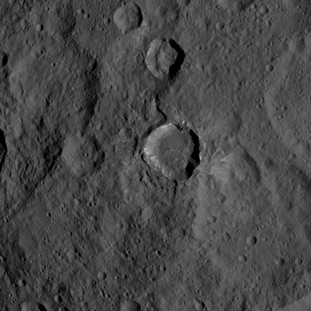 This view of Ceres from NASA's Dawn spacecraft shows a fresh impact crater with a flat floor. The crater is surrounded by smooth, flow-like ejecta that covers adjacent older impact craters. The crater is about 16 miles (26 kilometers) in diameter.