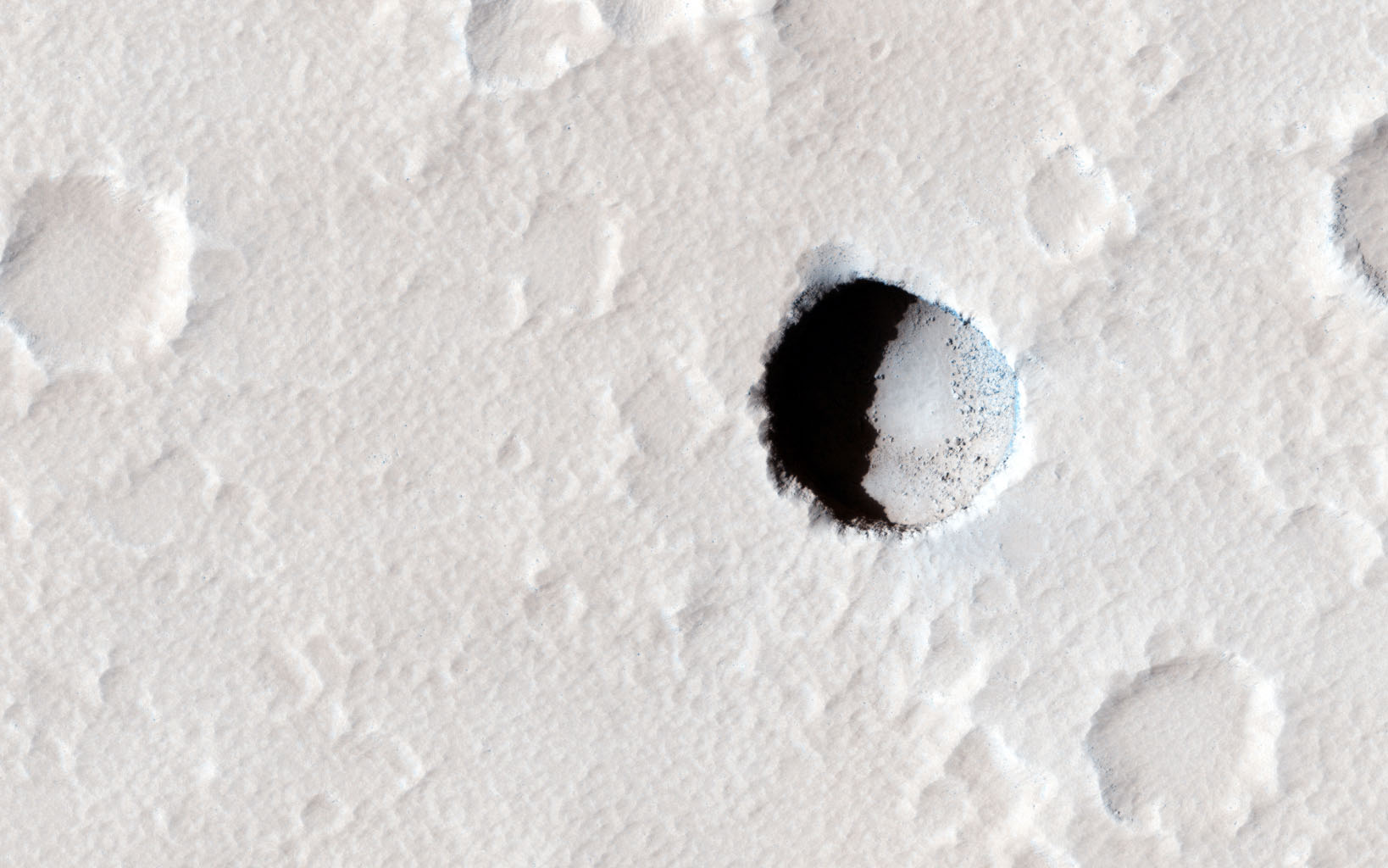 This image, taken by NASA's Mars Reconnaissance Orbiter spacecraft, is of an area on the lower southeastern flank of the volcano Elysium Mons. A small, dark pristine-appearing pit is clearly visible among the numerous small impact craters.