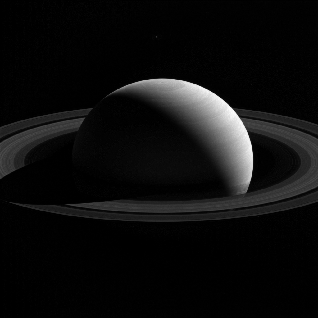 An illusion of perspective, Saturn's moon Tethys seems to hang above the planet's north pole in this view from NASA's Cassini spacecraft.