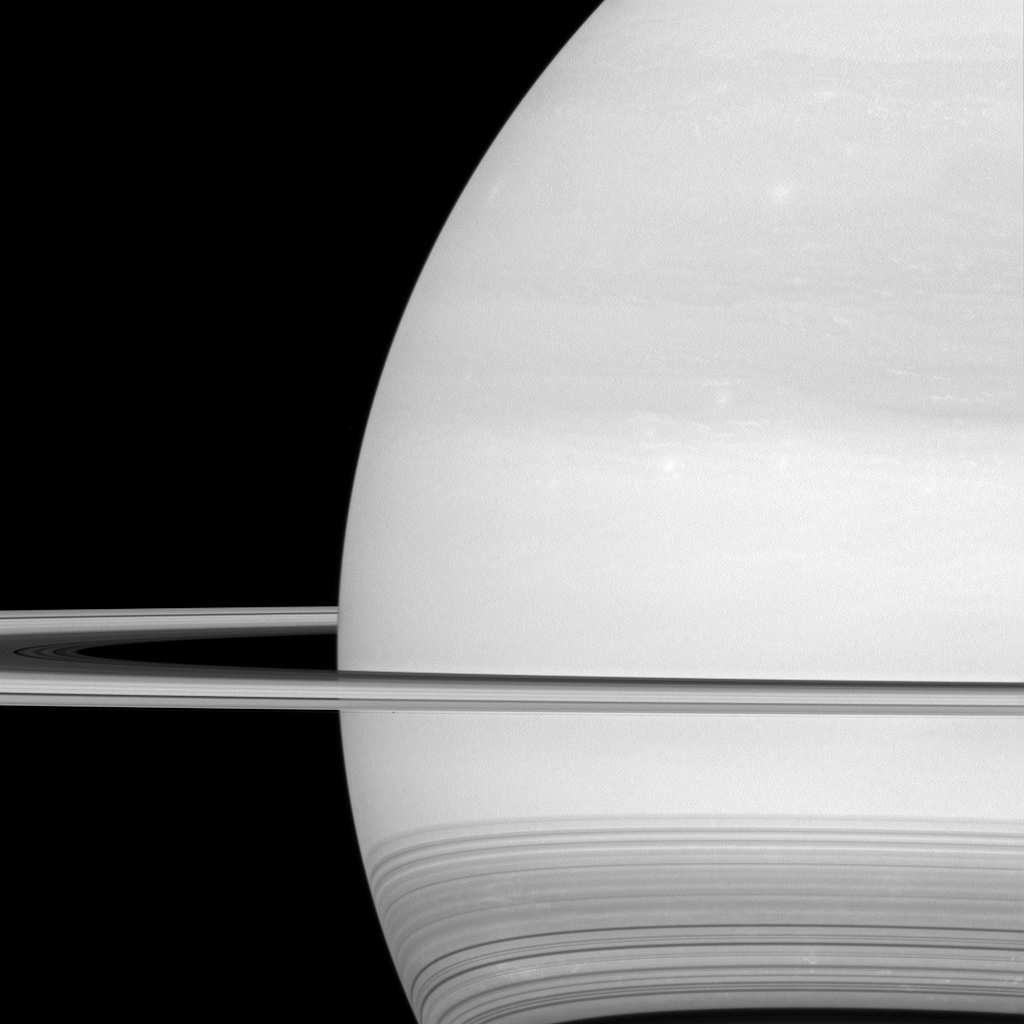 NASA's Cassini spacecraft looks toward the brilliant disk of Saturn, surrounded by the icy lanes of its rings. Faint wisps of cloud are visible in the atmosphere. At bottom, ring shadows trace delicate, curving lines across the planet.