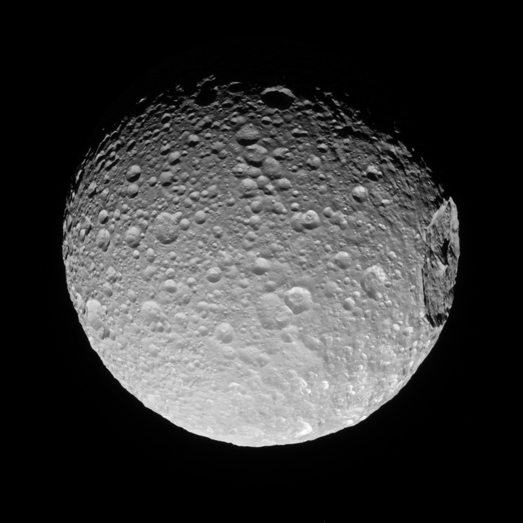 Mimas' gigantic crater Herschel lies near the moon's limb in this view from NASA's Cassini spacecraft.