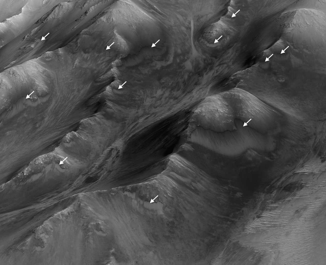 The white arrows indicate locations in this scene where numerous seasonal dark streaks have been identified in the Coprates Montes area of Mars' Valles Marineris by NASA's repeated MRO observations from orbit.