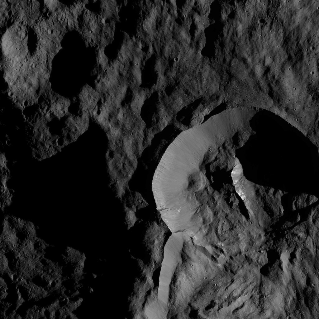 NASA's Dawn spacecraft captured this view on May 28, 2016, showing a relatively young crater with smooth walls and a sharp rim. The crater has a prominent central ridge, imprinted upon the rim of the larger Datan Crater, lying toward the lower right.