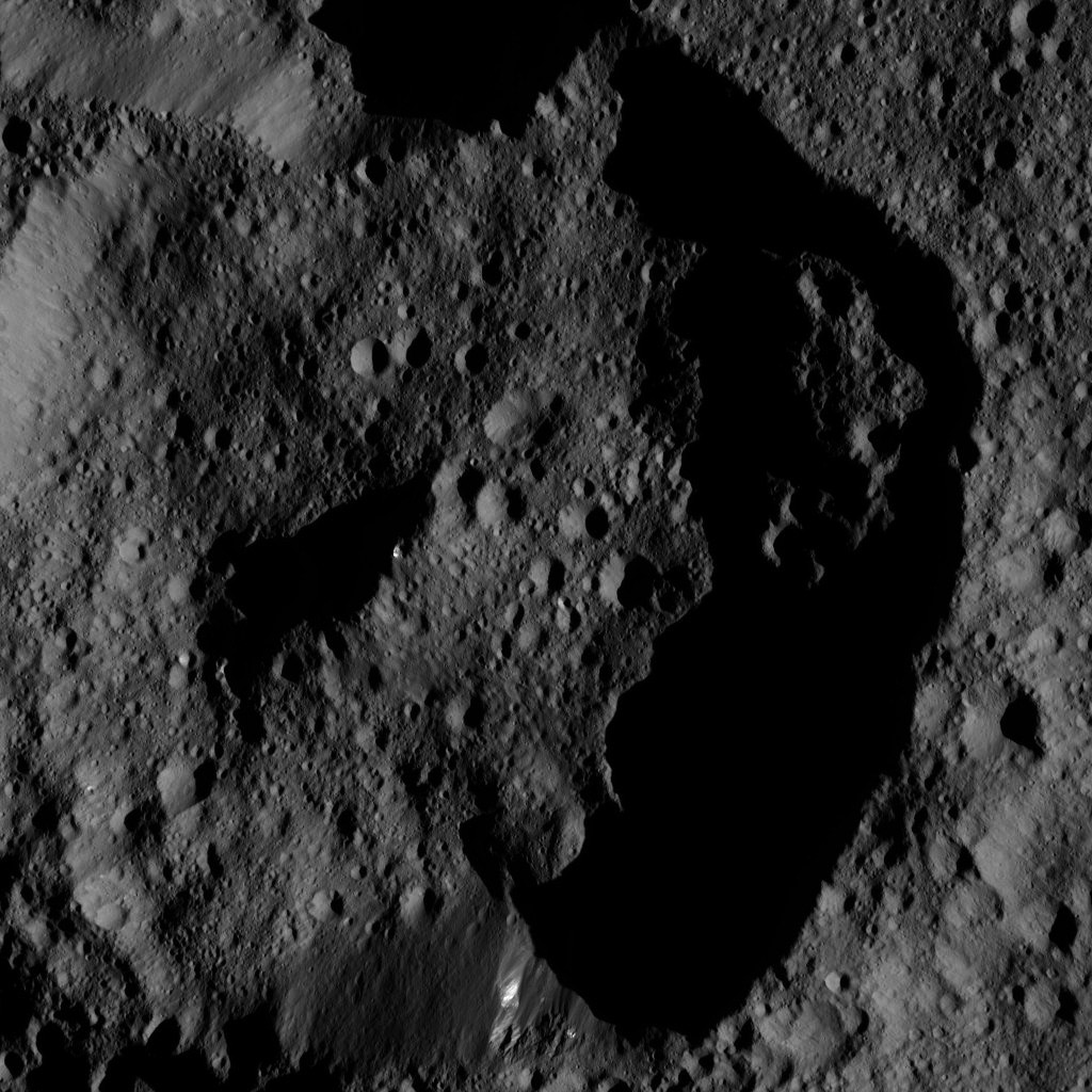 This image. taken on June 12, 2016, from NASA's Dawn spacecraft shows dimly lit, cratered terrain on Ceres. Bright streaks of material are visible on one section of the crater wall (at bottom), and near the top of its central peak.