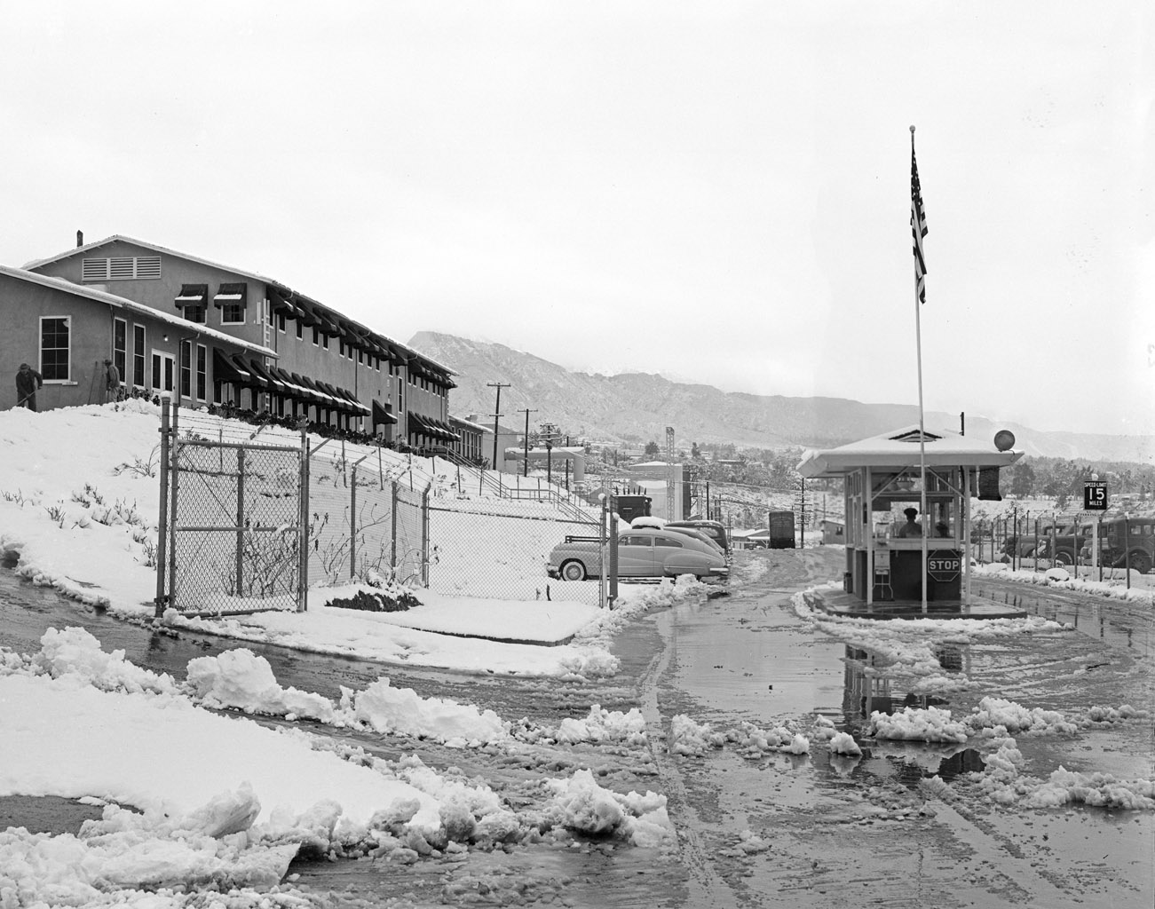 This archival photograph from 1949 shows the main entrance gate to the Jet Propulsion Laboratory in Pasadena, California, after a snowstorm. To the left is JPL's administration building at the time. Building 67 is the Materials Research Building today.