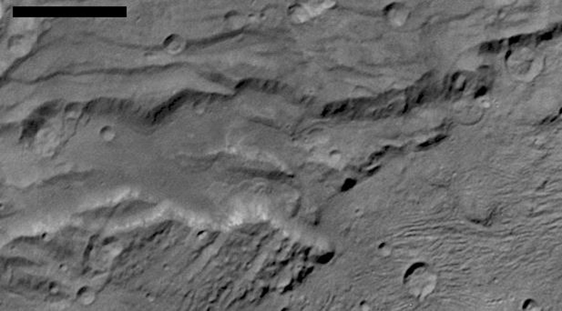 Scientists from NASA's New Horizons mission have spotted signs of long run-out landslides on Pluto's largest moon, Charon. This image is of Charon's informally named Serenity Chasma.