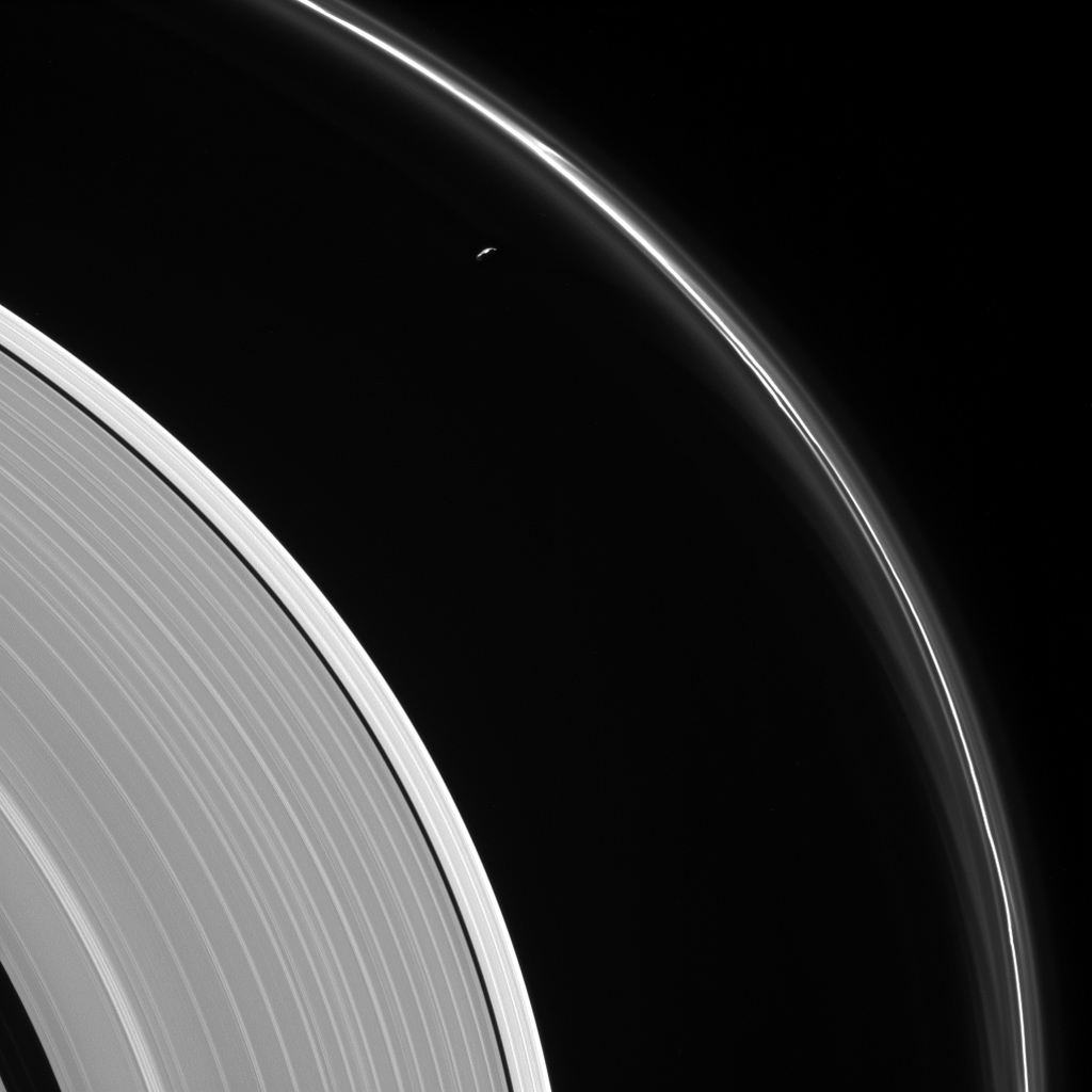 The thin sliver of Saturn's moon Prometheus lurks near ghostly structures in Saturn's narrow F ring in this view from NASA's Cassini spacecraft. Many of the narrow ring's faint and wispy features result from its gravitational interactions with Prometheus.