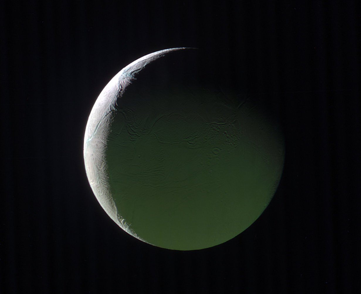The brightly lit limb of a crescent Enceladus looks ethereal against the blackness of space as seen by NASA's Cassini's spacecraft. The rest of the moon, lit by light reflected from Saturn, presents a ghostly appearance.
