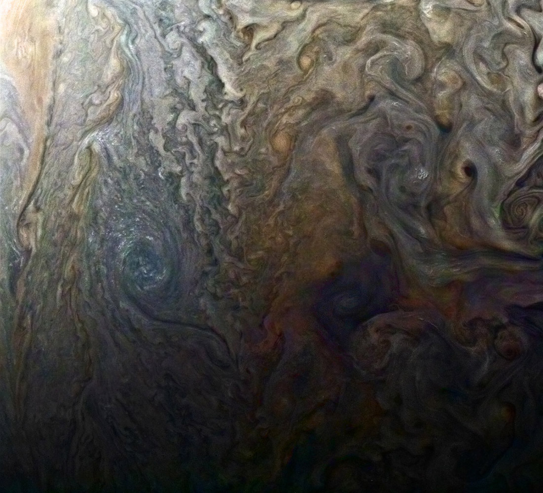 This enhanced-color image from NASA's Juno spacecraft of a mysterious dark spot on Jupiter seems to reveal a Jovian 'galaxy' of swirling storms.