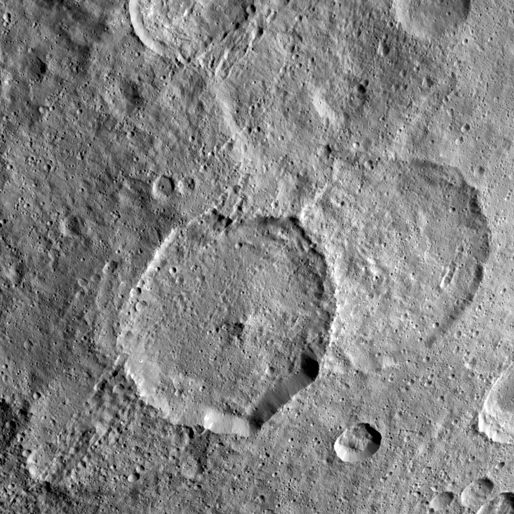 Inamahari Crater on Ceres, the large well-defined crater at the center of this image from NASA's Dawn spacecraft, is one of the sites where scientists have discovered evidence for organic material.