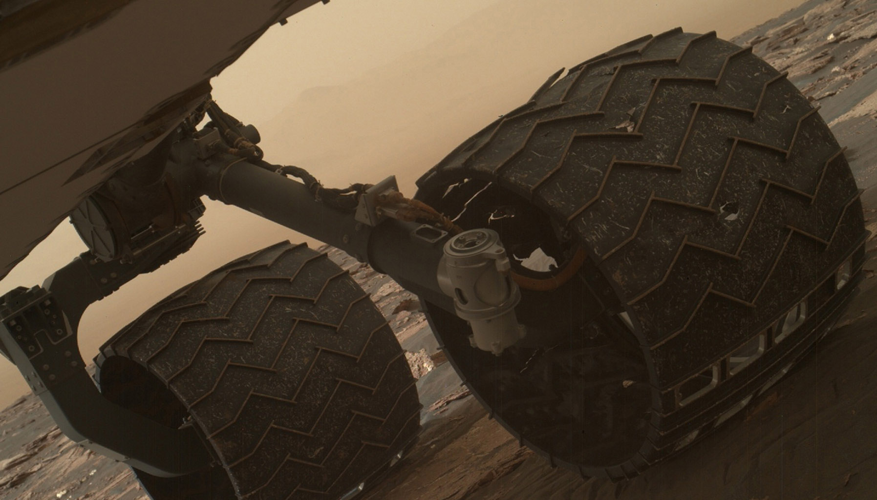 Two of the raised treads, called grousers, on the left middle wheel of NASA's Curiosity Mars rover broke during the first quarter of 2017, seen is the partially detached at the top of the wheel in this image from the MAHLI camera on the rover's arm.