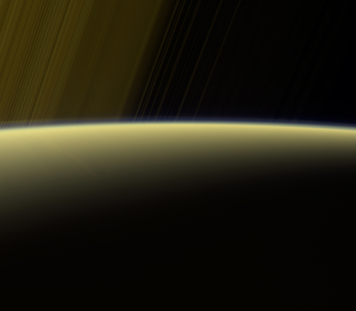 This false-color view from NASA's Cassini spacecraft gazes toward the rings beyond Saturn's sunlit horizon, where a thin haze can be seen along the limb.