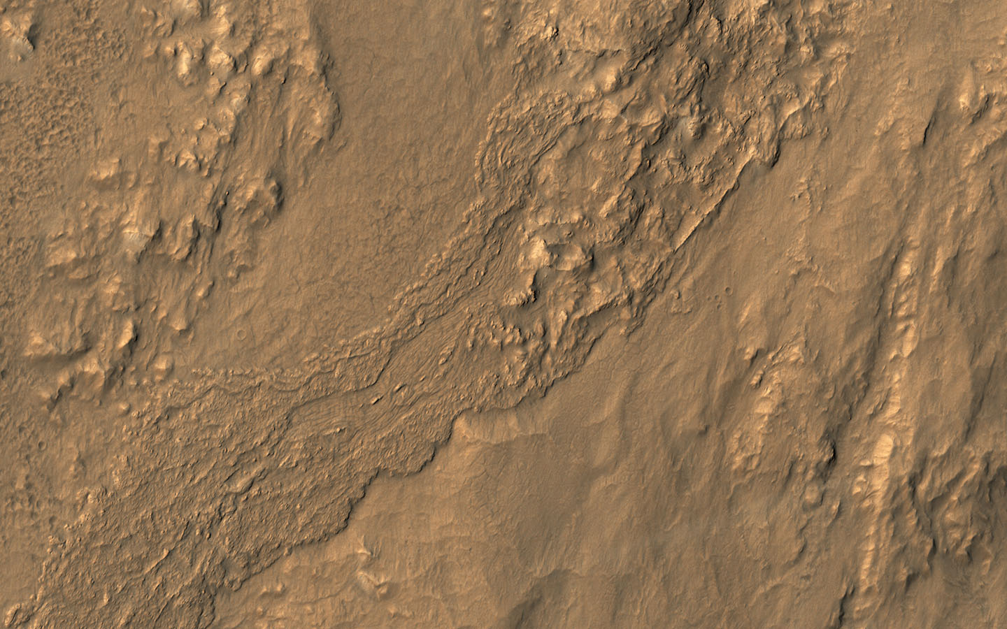 This oblique view from NASA's Mars Reconnaissance Orbiter shows a small part of the near-rim ejecta from Tooting Crater which must be either melted rock from the impact event, or a wet debris flow from melting of ice.