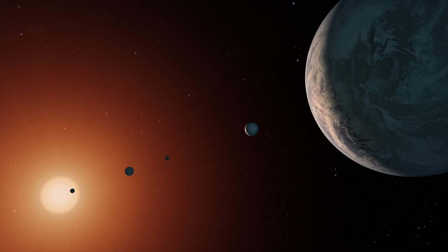 This artist's concept shows what the TRAPPIST-1 planetary system may look like from a vantage point near planet TRAPPIST-1f (at right).