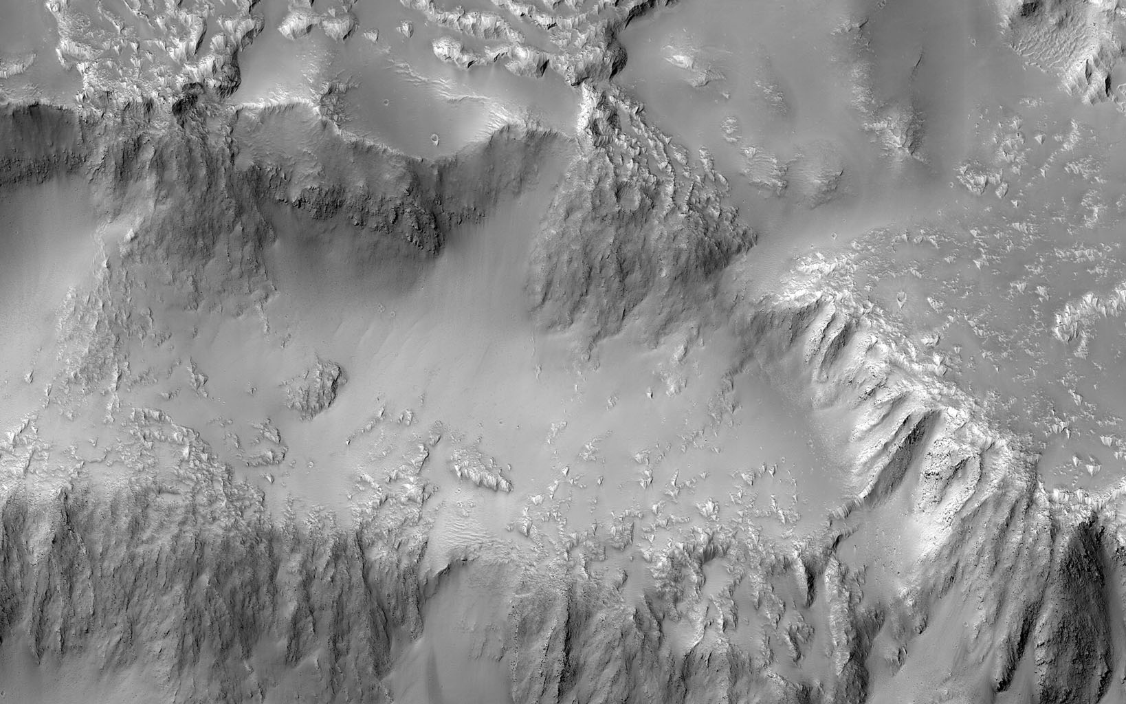 This image from NASA's Mars Reconnaissance Orbiter shows the northern rim of a 30-kilometer diameter crater situated in the western part of the Tharsis volcanic province.