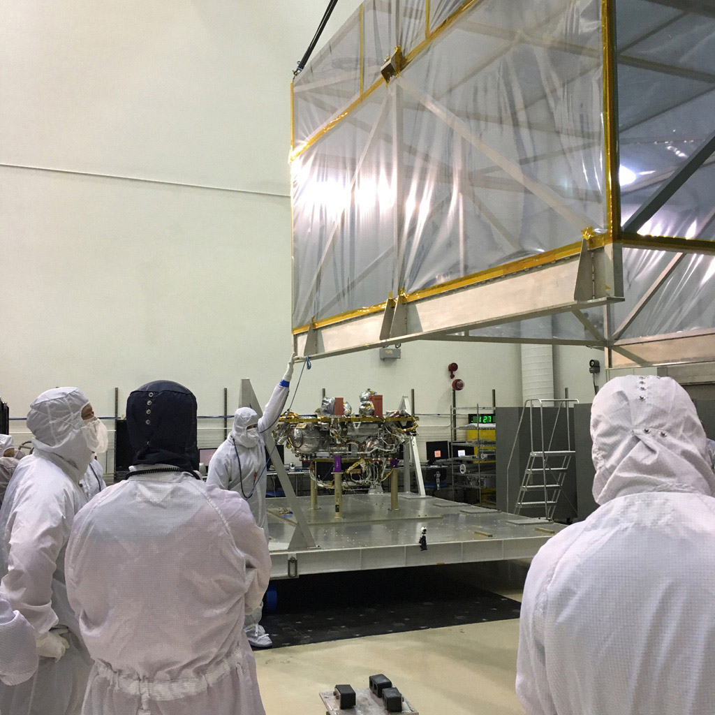 Members of the InSight mission's assembly, test and launch operations (ATLO) team remove the 'birdcage' from NASA's InSight spacecraft.