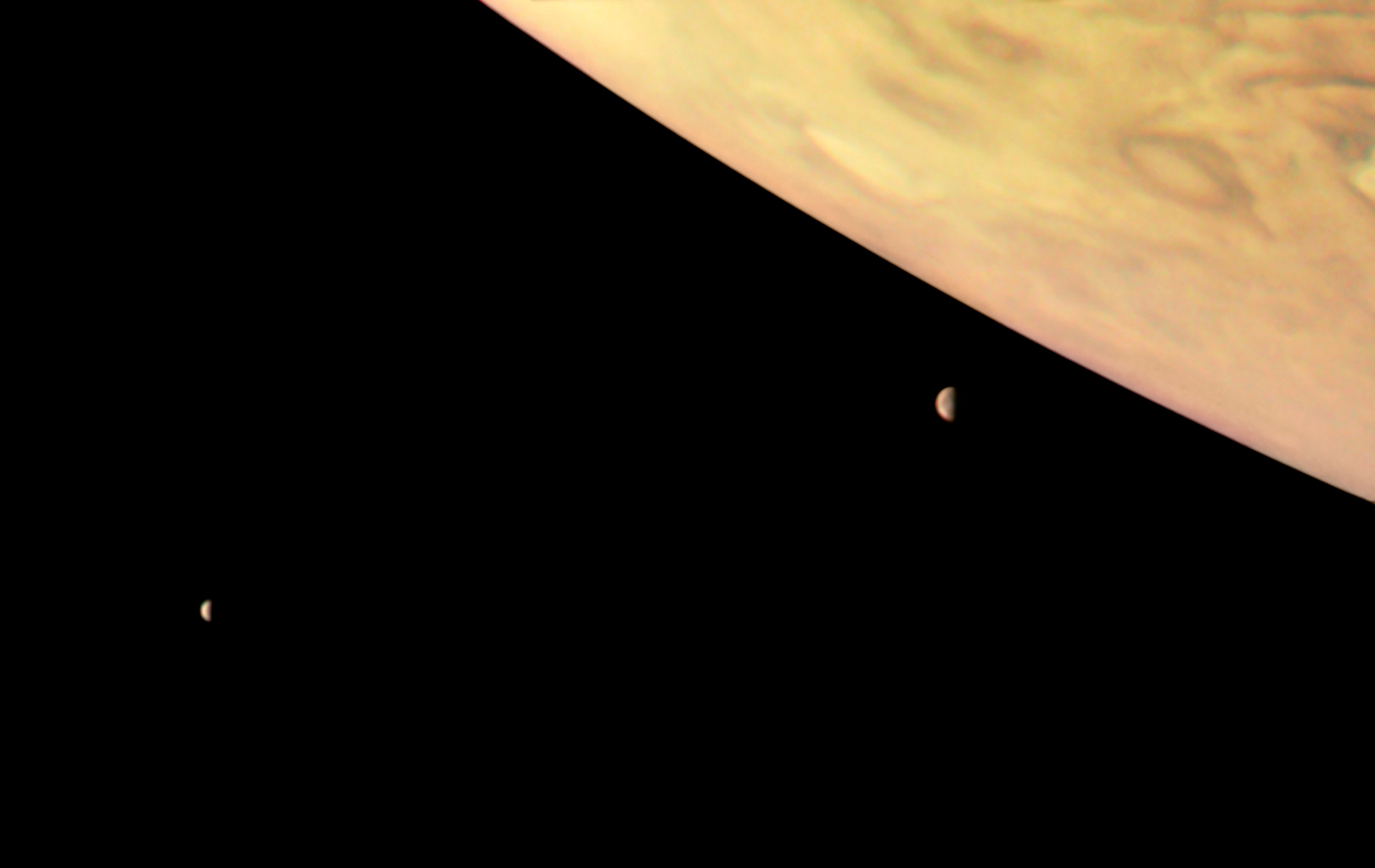 This color-enhanced image of Jupiter and two of its largest moons, Io and Europa, was captured by NASA's Juno spacecraft as it performed its eighth flyby of the gas giant planet.