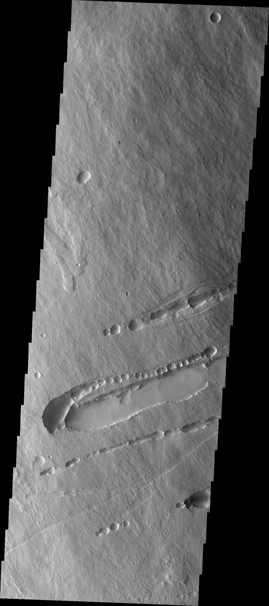 This image from NASA's 2001 Mars Odyssey spacecraft shows part of the southeastern flank of Pavonis Mons. Surface lava flows run down hill from the top left of the image to the bottom right.