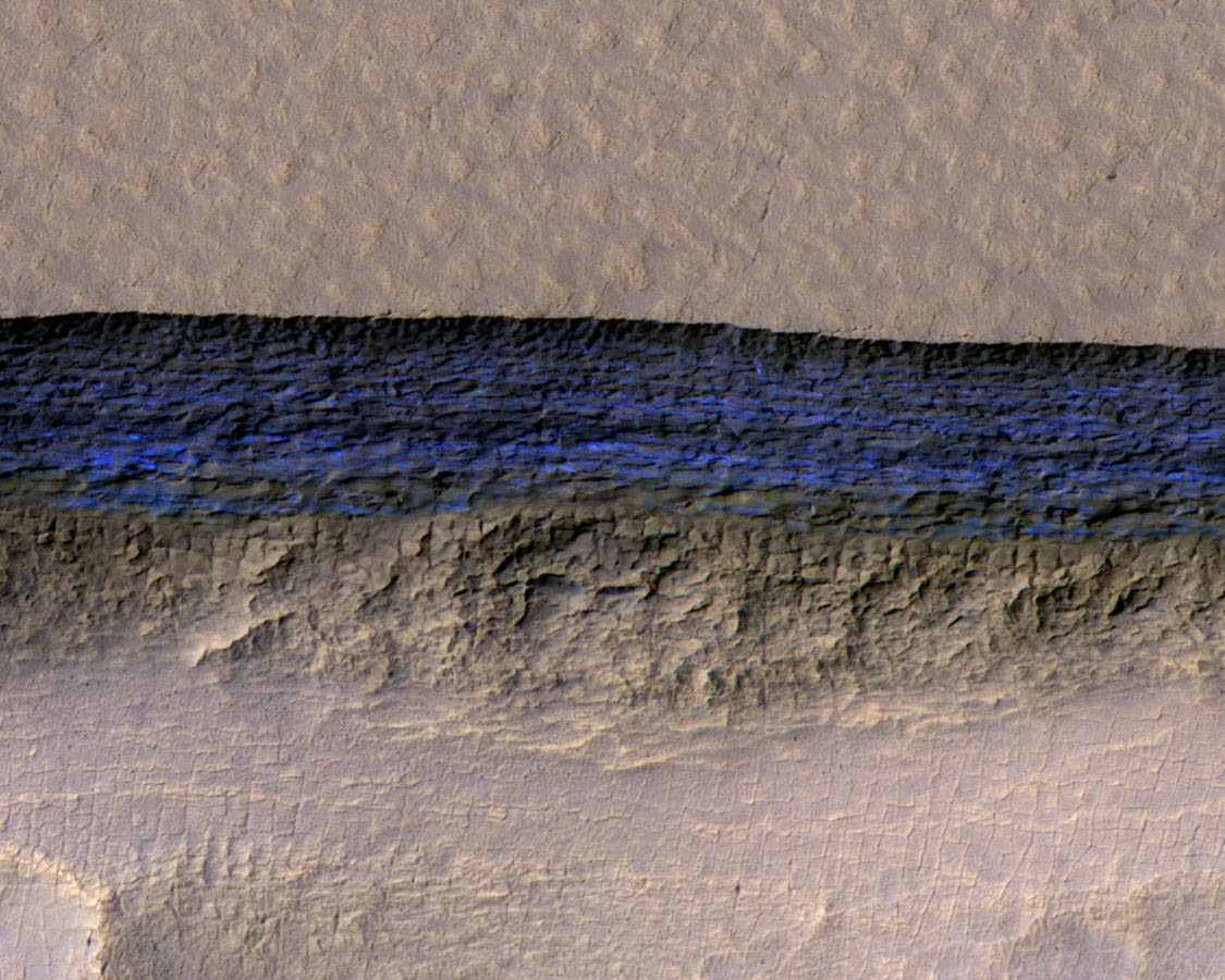 A cross-section of a thick sheet of underground ice is exposed at the steep slope (or scarp) that appears bright blue in this enhanced-color view from NASA's Mars Reconnaissance Orbiter.