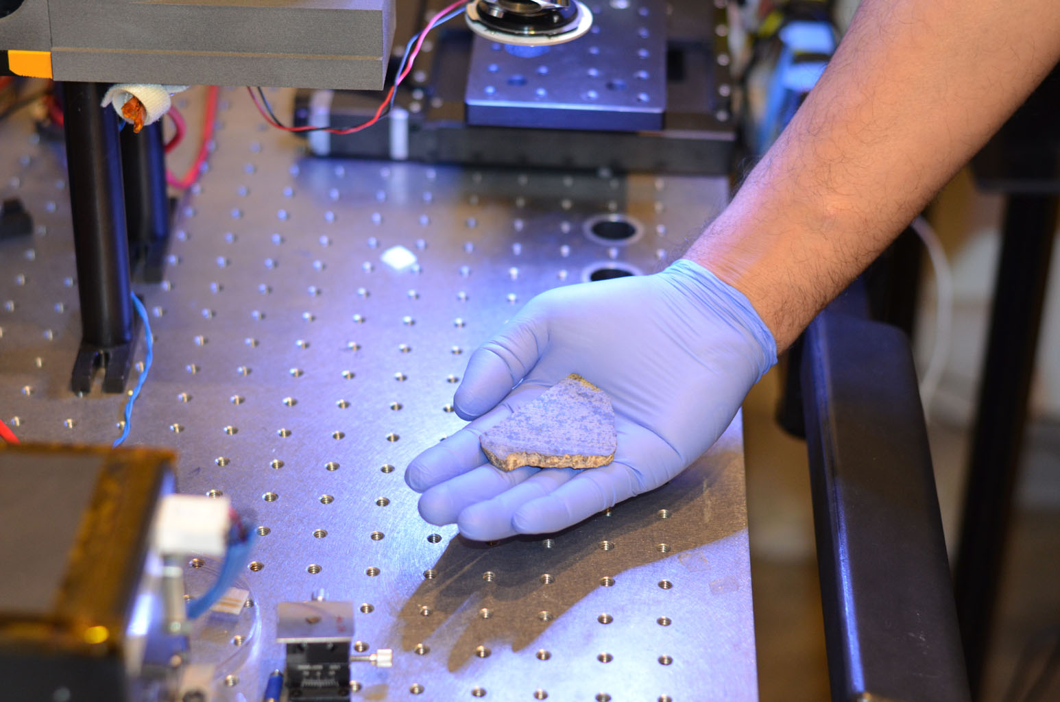 Rohit Bhartia of NASA's Mars 2020 mission holds a slice of a meteorite scientists have determined came from Mars. This slice will likely be used here on Earth for testing a laser instrument for NASA's Mars 2020 rover.