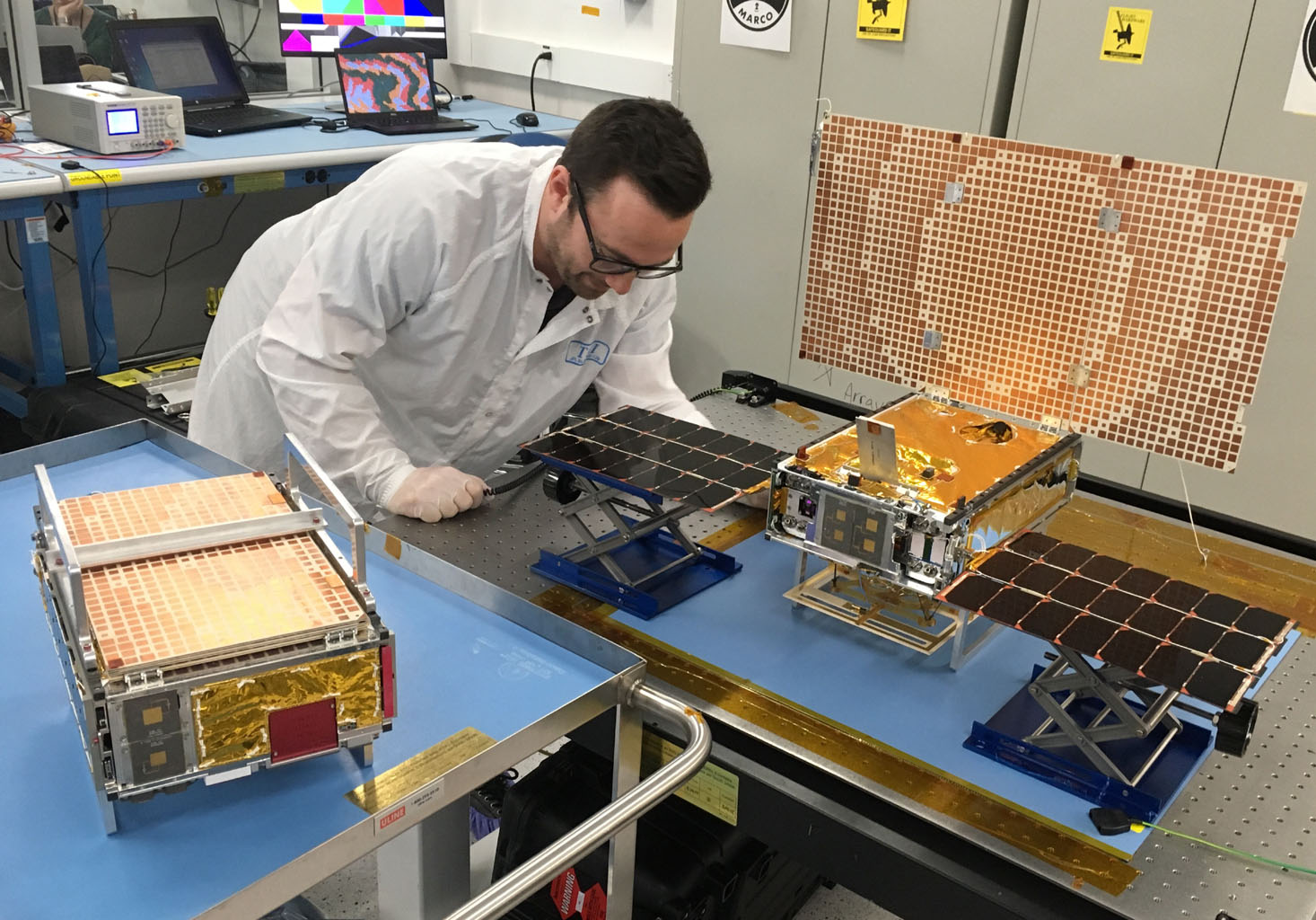 Engineer Joel Steinkraus stands with both of the Mars Cube One (MarCO) spacecraft at NASA's Jet Propulsion Laboratory.