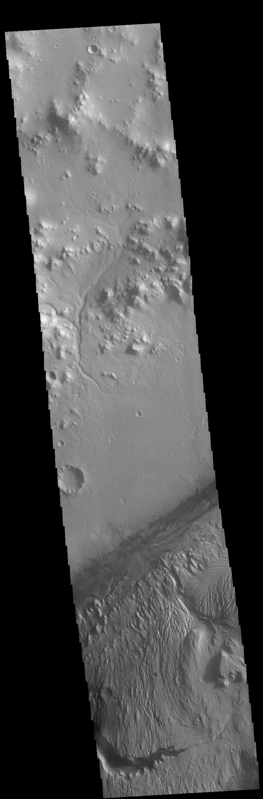 This image of Gale Crater from NASA's 2001 Mars Odyssey spacecraft shows part of the huge layered deposit that covers much of the crater floor. The top of the image shows part of the crater rim, including one of the many small channels.