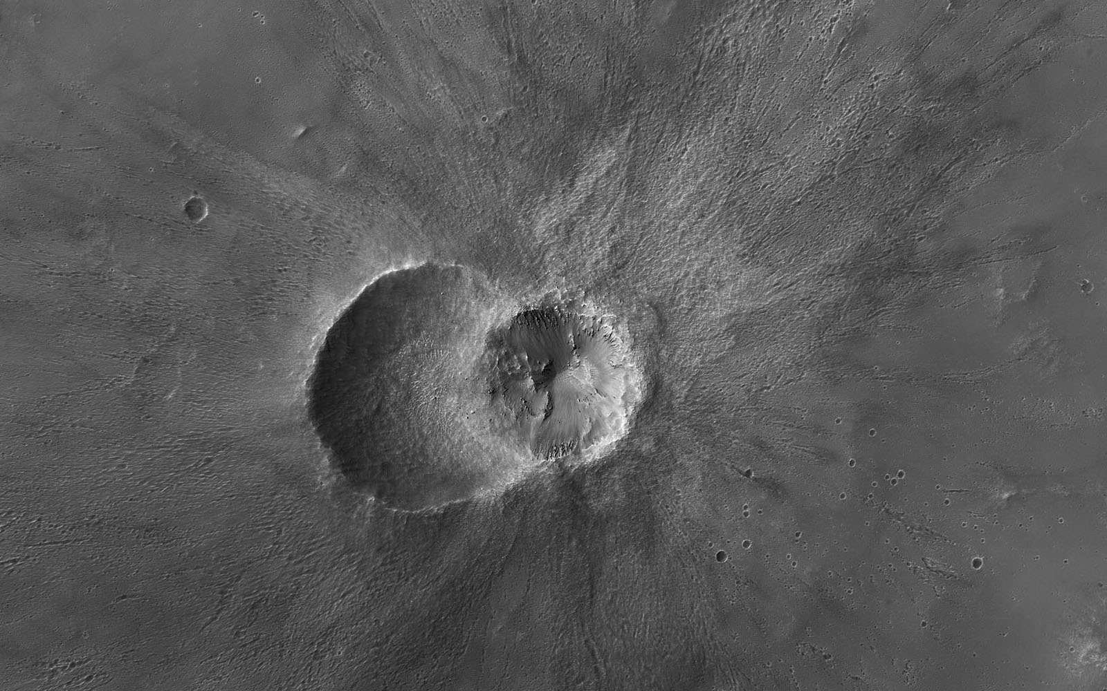 This image from NASA's Mars Reconnaissance Orbiter (MRO) shows two small impact craters located in Meridiani Planum on Mars. Small boulders on the floor and walls of the left-side crater.