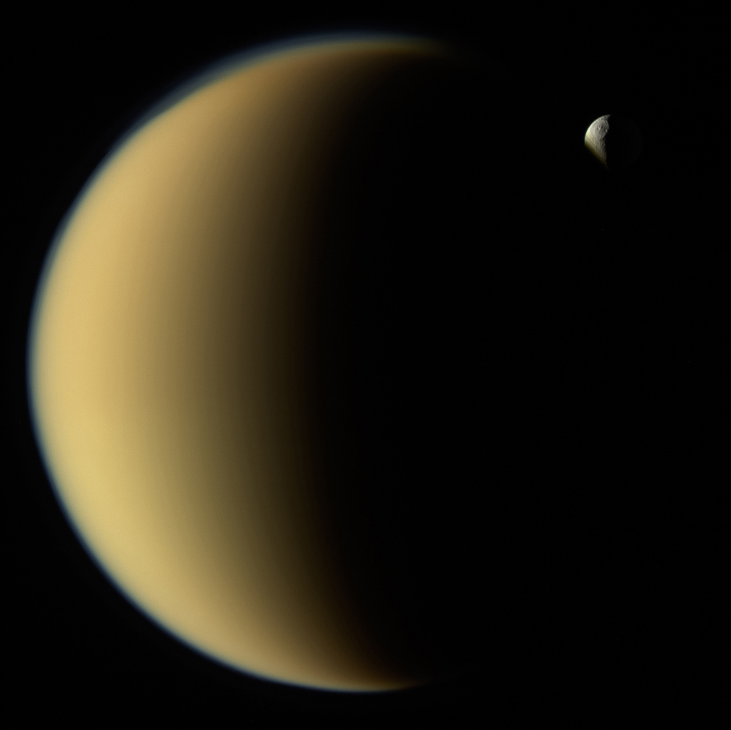 This image from NASA's Cassini spacecraft shows Saturn's moon Tethys disappearing behind Titan as observed by Cassini on Nov. 26, 2009. Tethys is about 660 miles (1,070 kilometers) across.