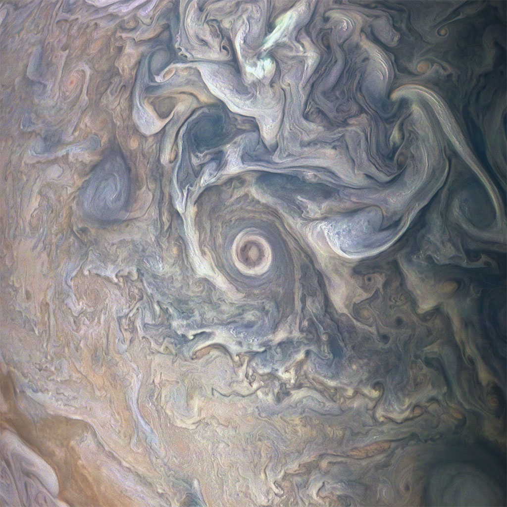 Intricate swirls in Jupiter's volatile northern hemisphere are captured in this image from NASA's Juno spacecraft. Bursts of scattered bright-white 'pop-up' clouds appear with some visibly casting shadows on the neighboring cloud layers beneath them.