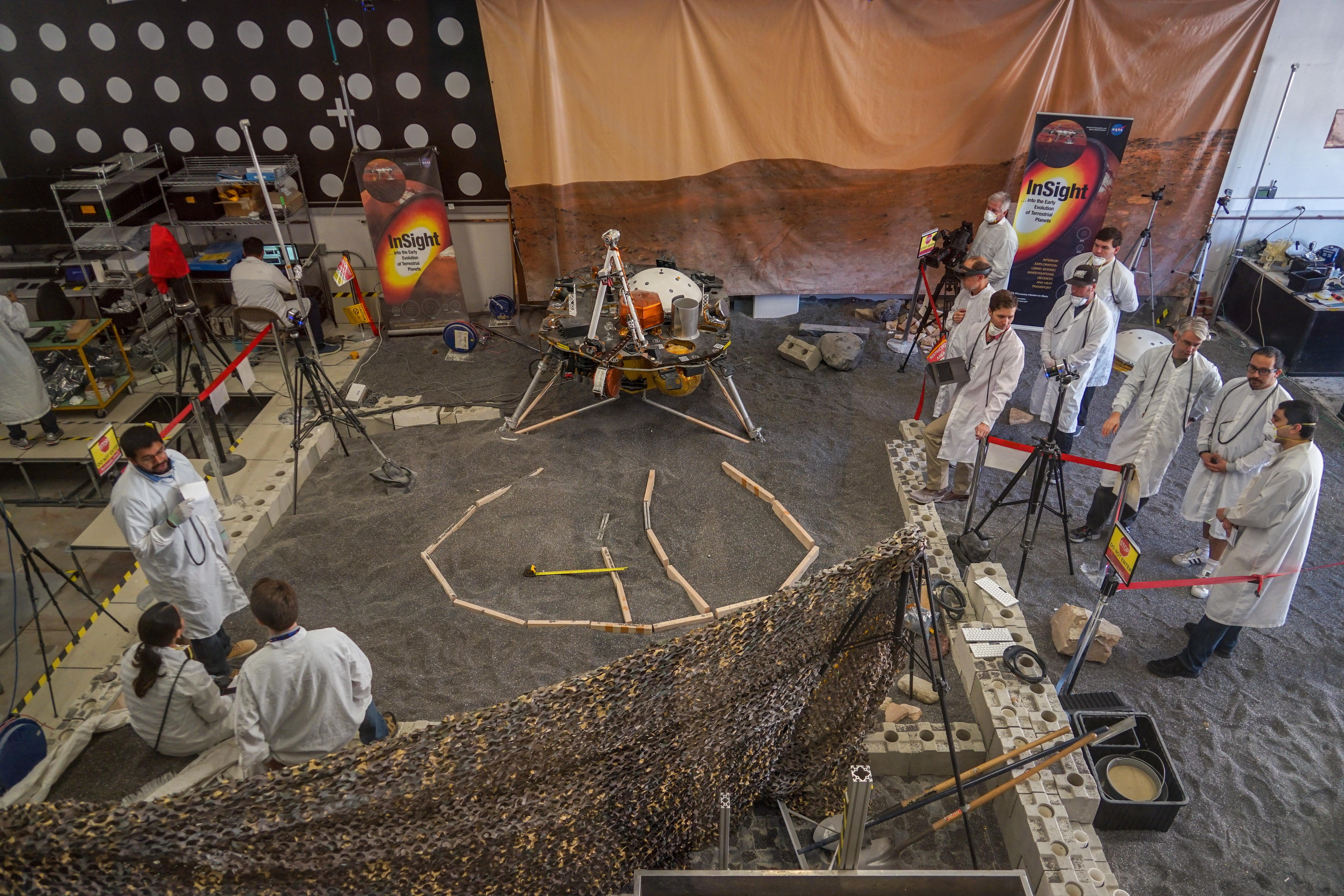 Engineers in Pasadena, California, sculpt a gravel-like material to mimic the terrain in front of NASAs InSight lander on Mars.