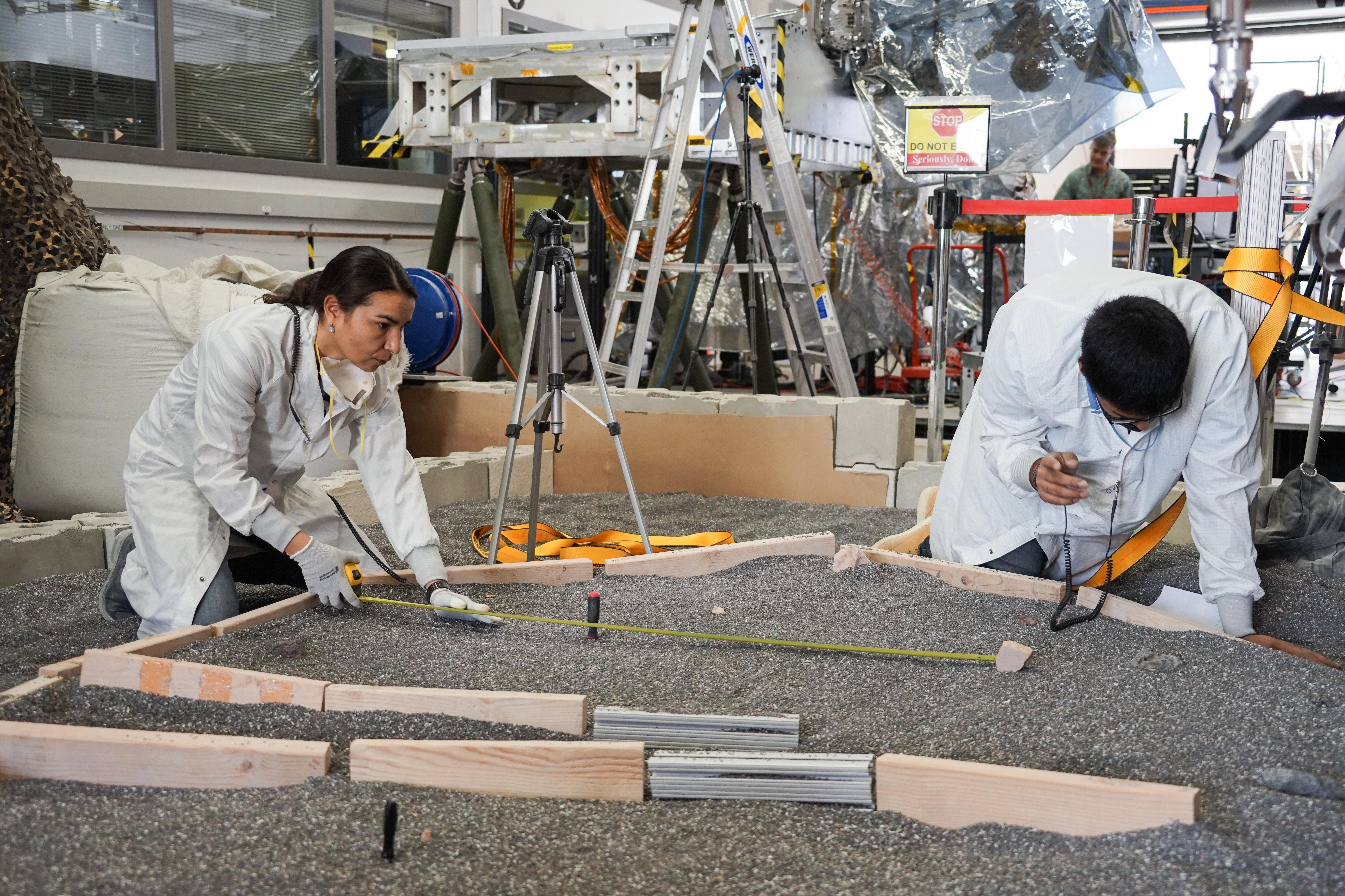 Engineers measure their test landers workspace -- the terrain where scientists want to set InSights instruments -- at NASAs Jet Propulsion Laboratory in Pasadena, California.