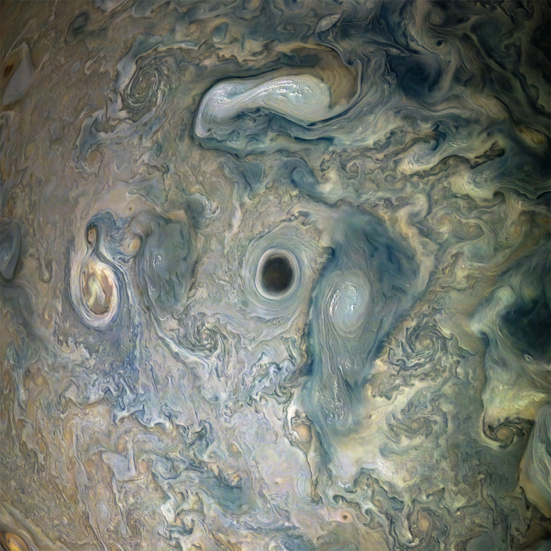 NASAs Juno spacecraft captured this view of an area within a Jovian jet stream showing a vortex that has an intensely dark center.