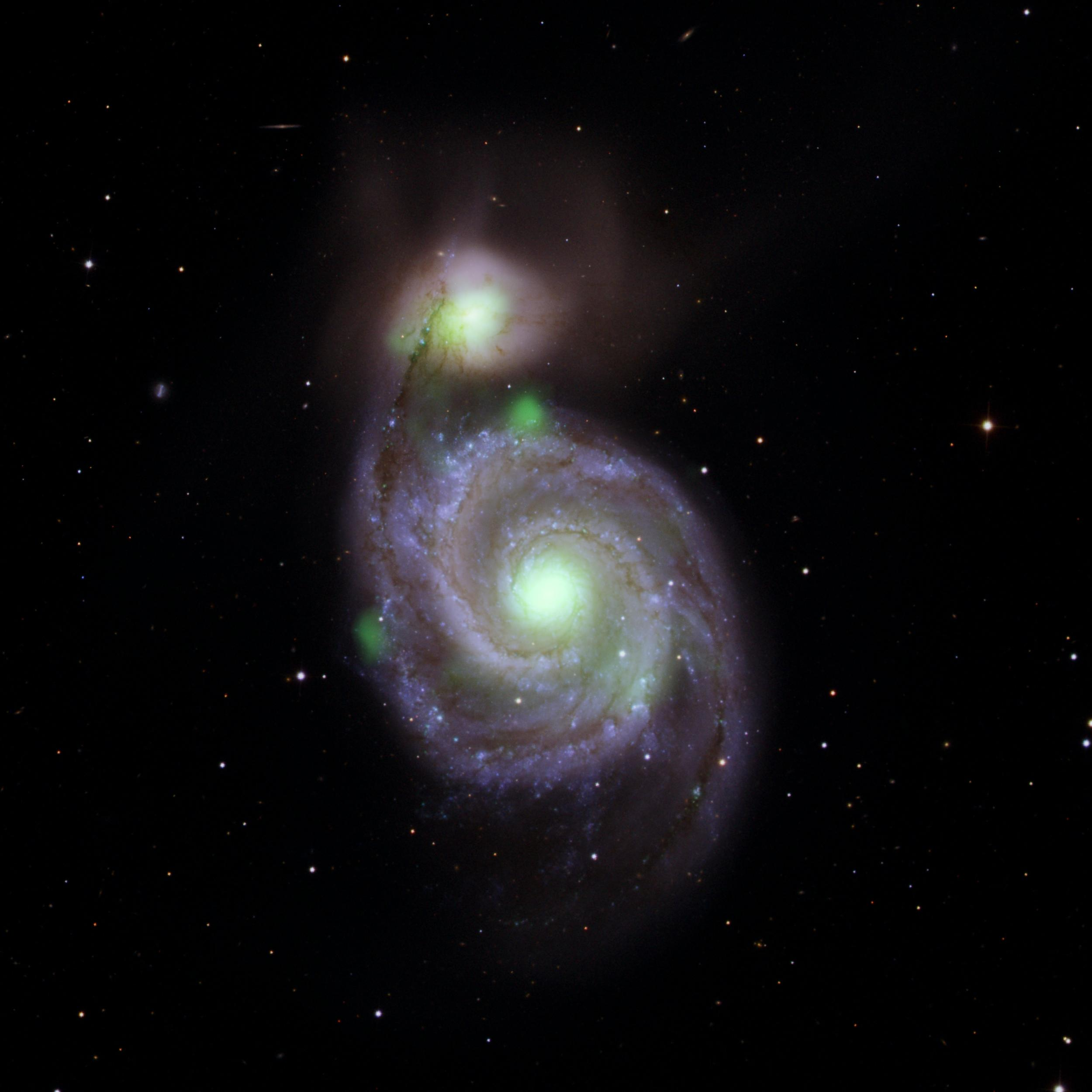 Sources of high-energy X-ray light captured by NASAs NuSTAR mission are overlaid on an image of the Whirlpool galaxy and its companion galaxy, M51b, taken by the Sloan Digital Sky Survey.