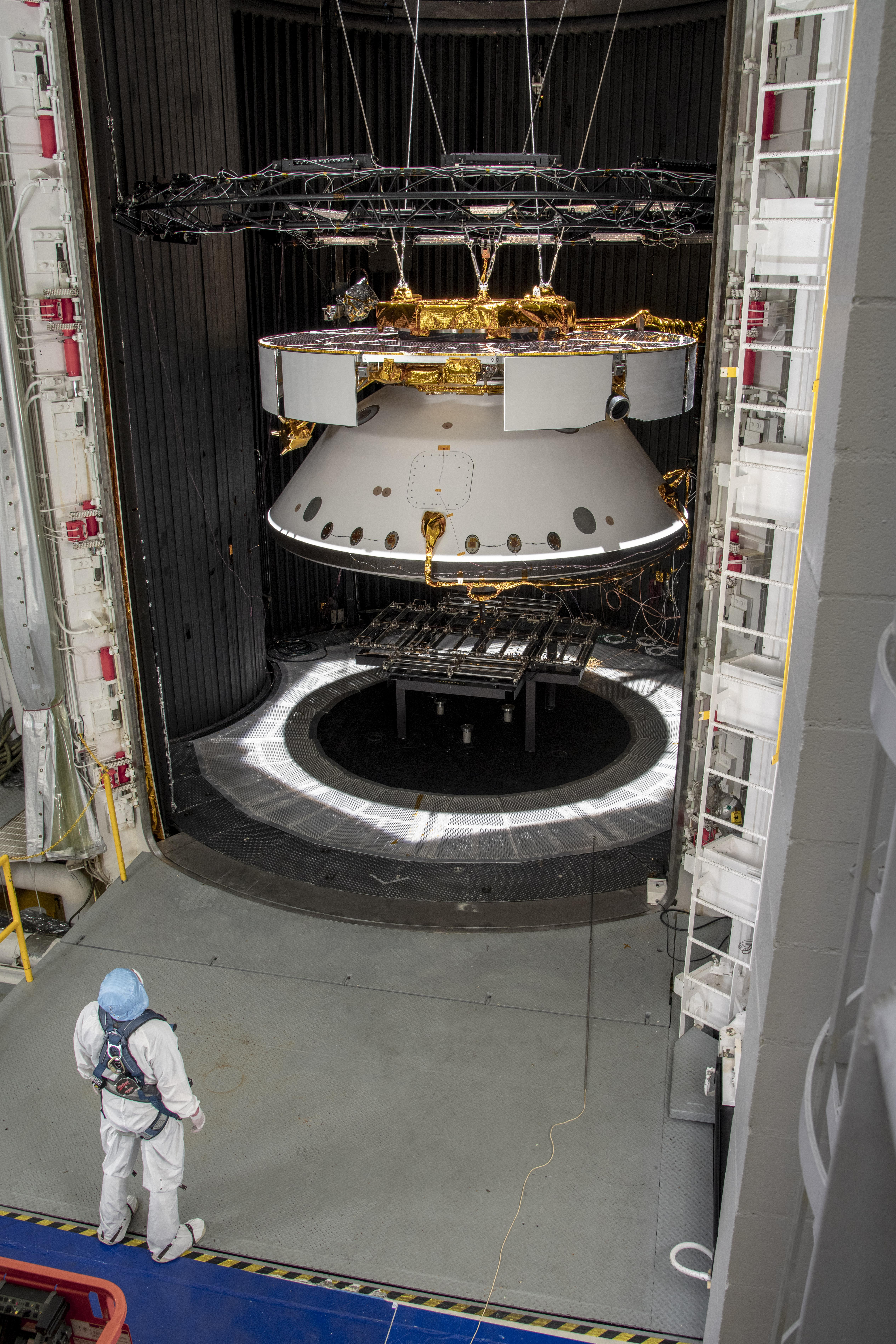 An engineer inspects the completed spacecraft that will carry NASAs next Mars rover to the Red Planet, prior to a test in the Space Simulator Facility at NASAs Jet Propulsion Laboratory in Pasadena, California.
