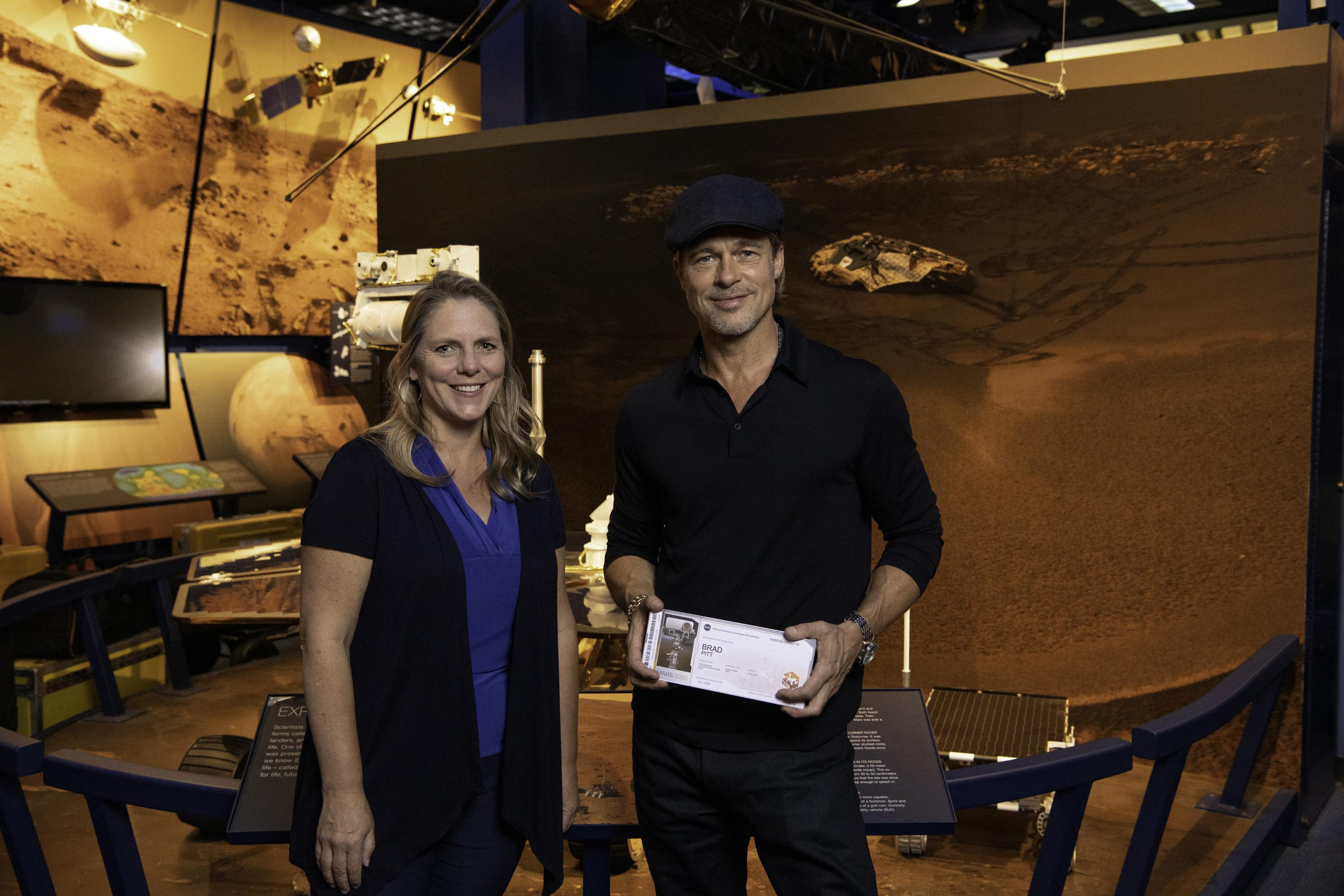 The actor Brad Pitt (right) shows off his boarding pass for Mars with Jennifer Trosper (left), the Mars 2020 project systems engineer, at JPL on Sept. 6, 2019.