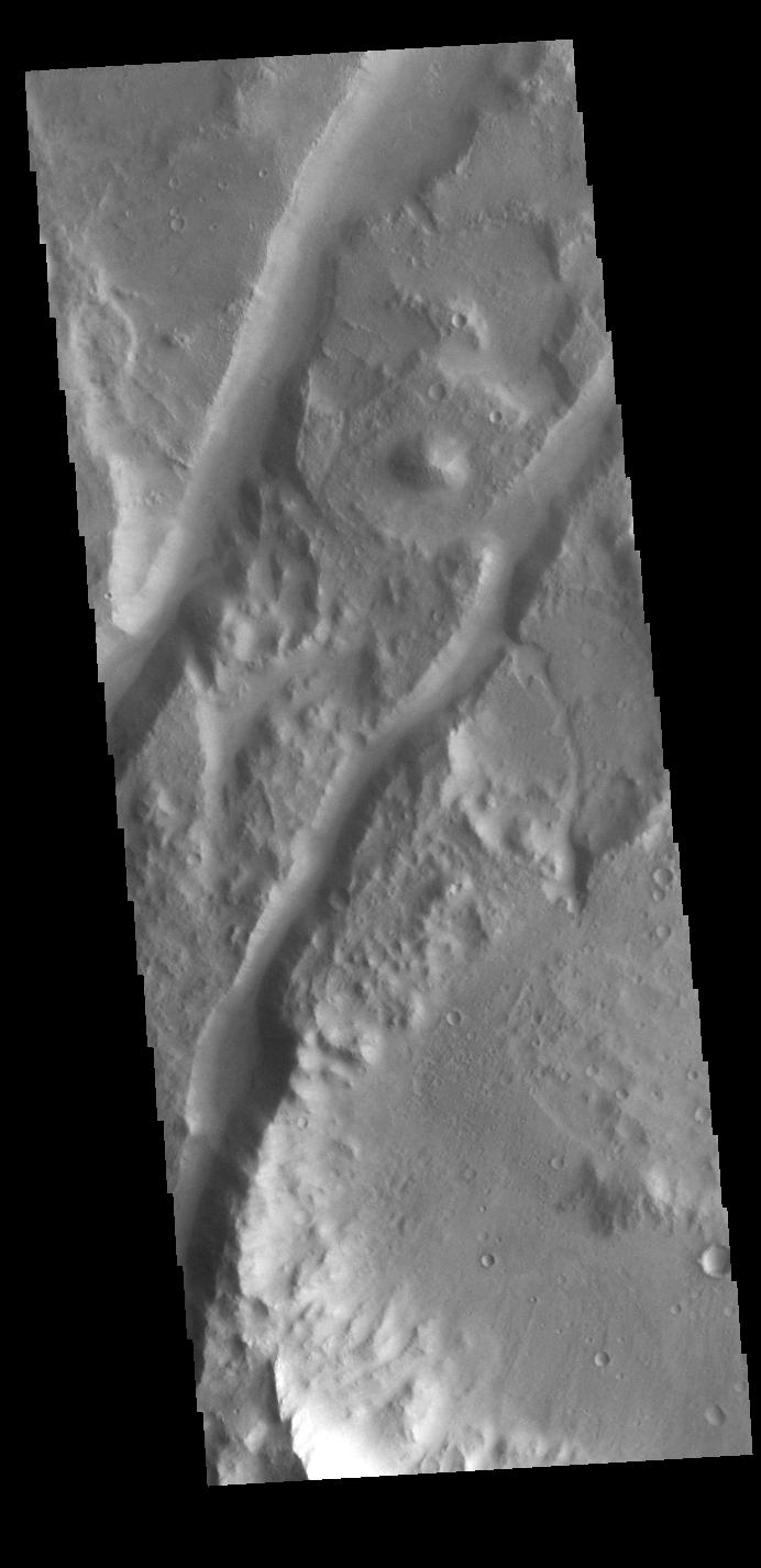 This image from NASAs Mars Odyssey shows two linear depressions, graben, created by tectonic activity.