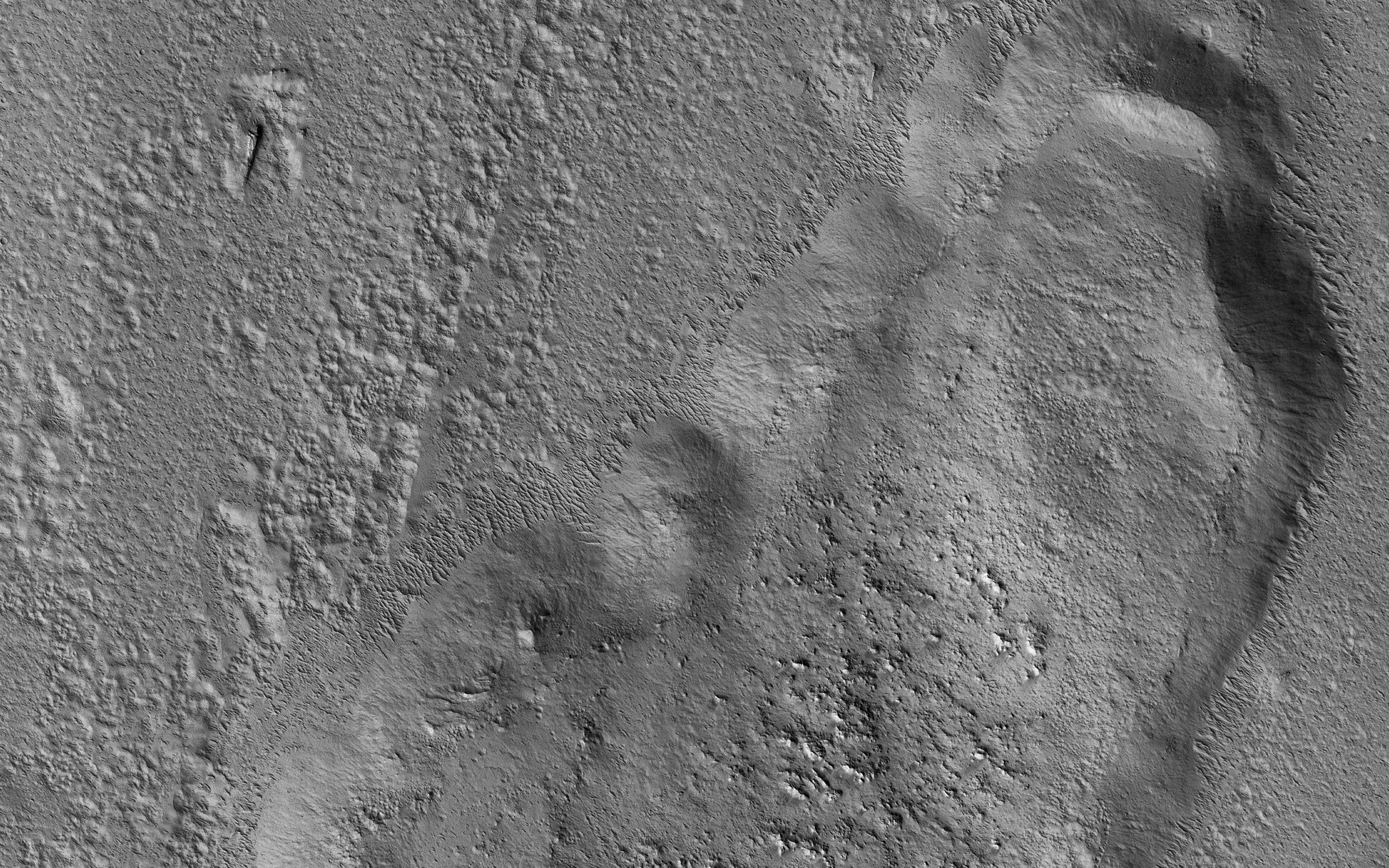 This image acquired on September 24, 2018 by NASAs Mars Reconnaissance Orbiter, shows a huge tongue-like form, which looks a like a mudflow with boulders on its surface.