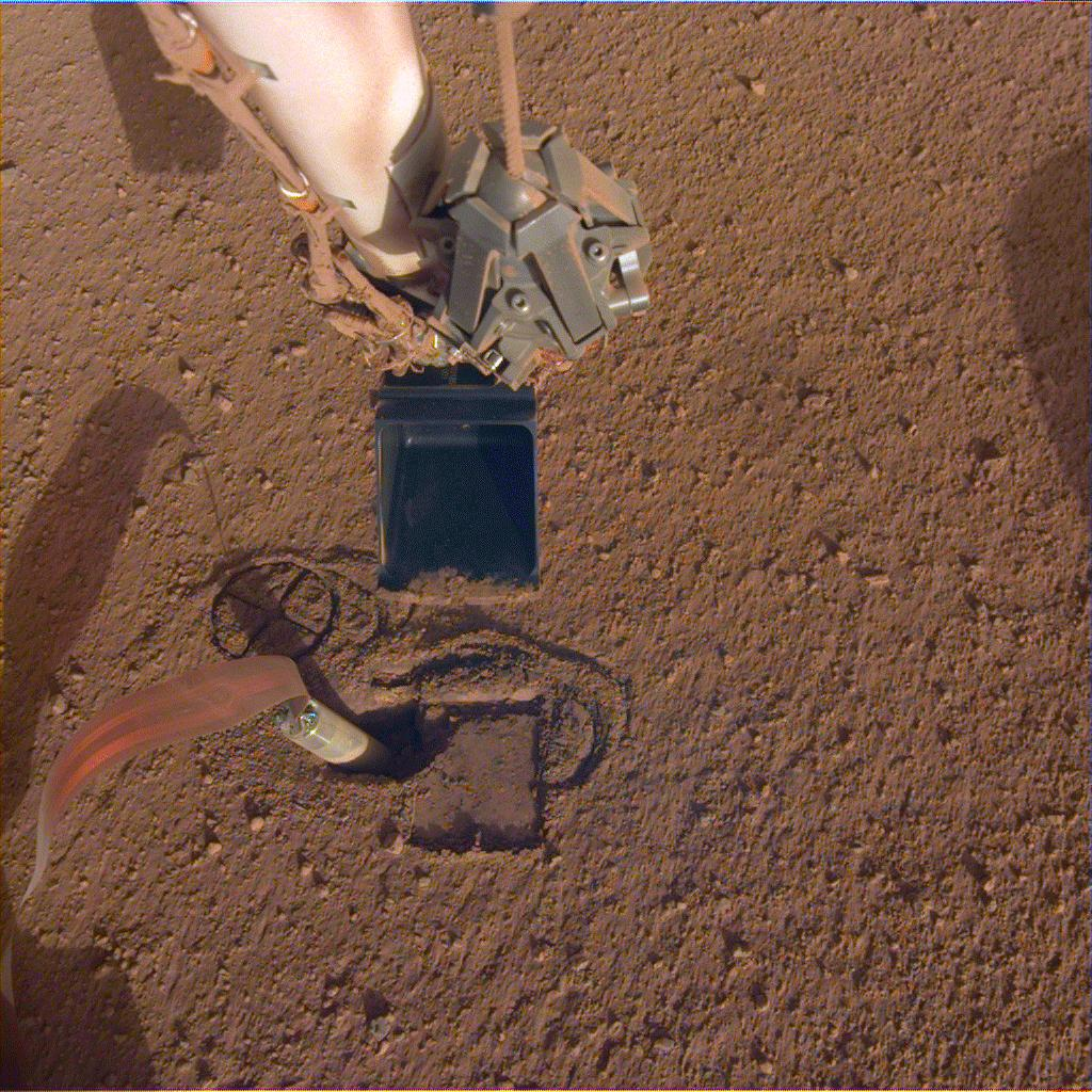 NASA InSights robotic arm will use its scoop to pin the spacecrafts heat probe, or mole, against the wall of its hole.