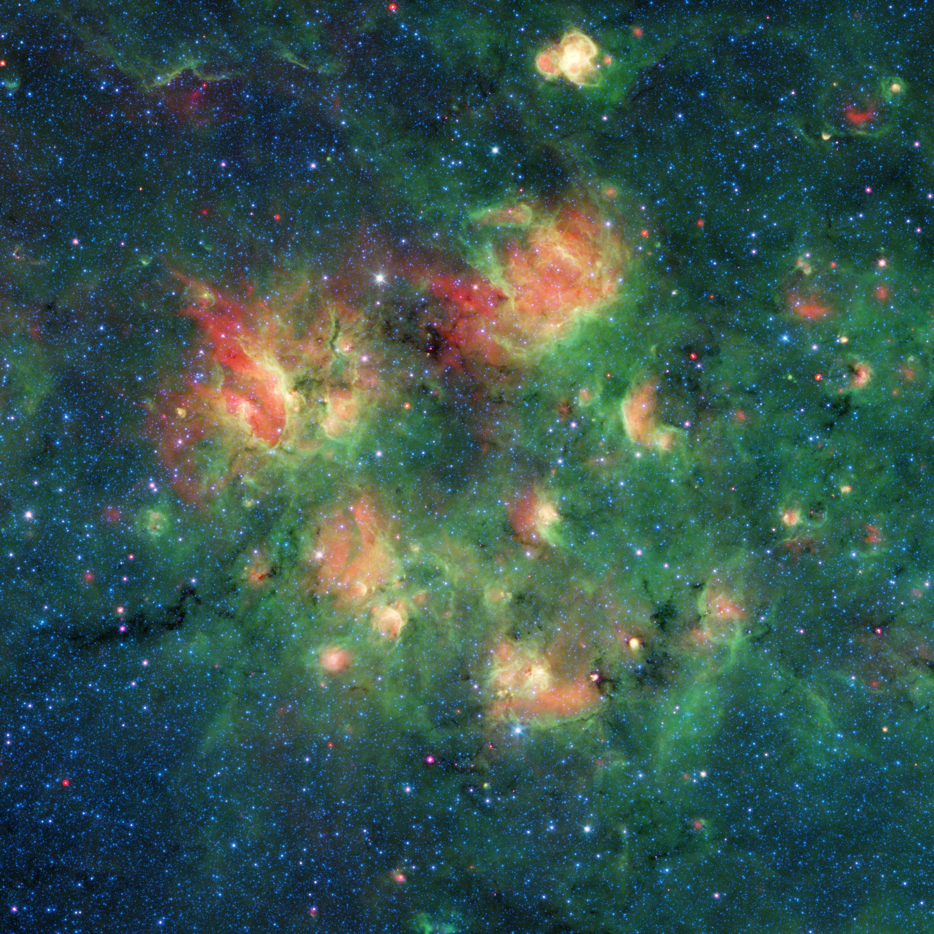 This infrared image from NASAs Spitzer Space Telescope shows a cloud of gas and dust full of bubbles, which are inflated by wind and radiation from massive young stars.