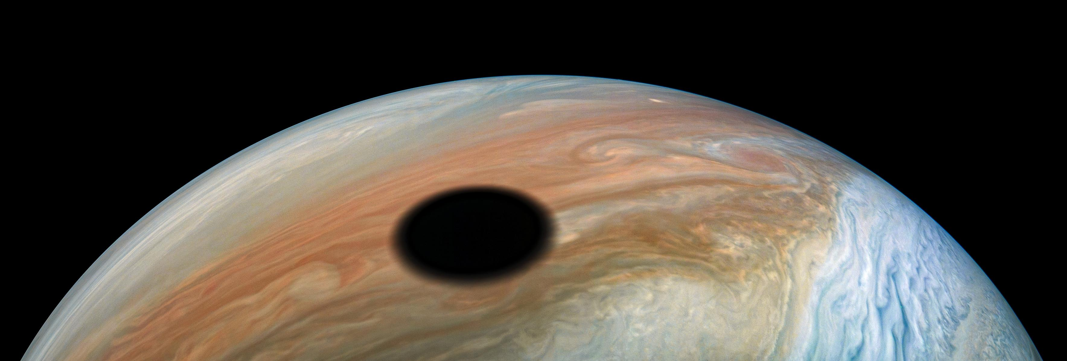 Jupiters volcanically active moon Io casts its shadow on the planet in this dramatic image from NASAs Juno spacecraft.