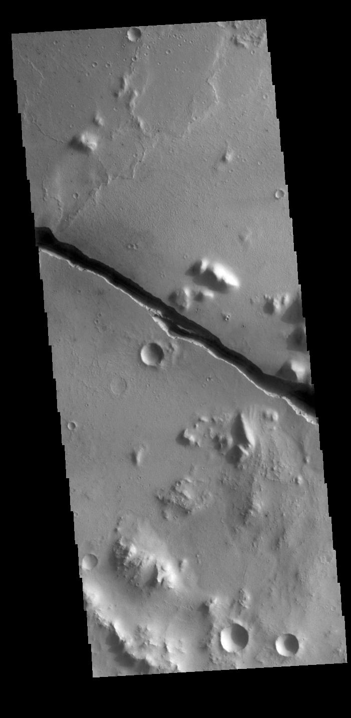 This image from NASAs Mars Odyssey shows part of Cerberus Fossae. These large graben cut across the Tartarus Montes in Elysium Planitia.
