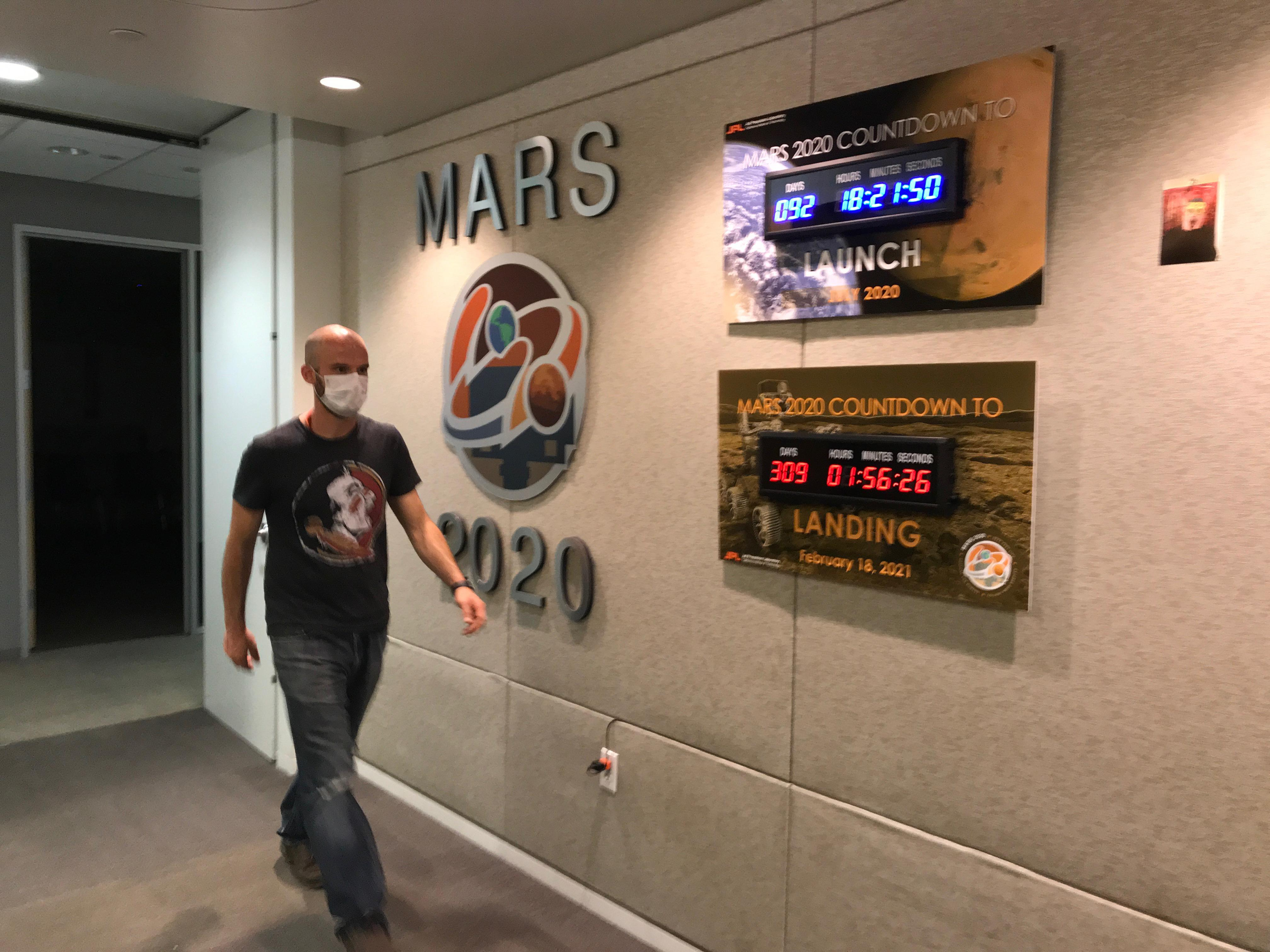 Ian Clark walks past mission countdown clocks in the Perseverance offices at JPL. Clark was needed on-Lab to supervise the assembly and cleaning of the sample tubes that will hold Martian sediment and rock.