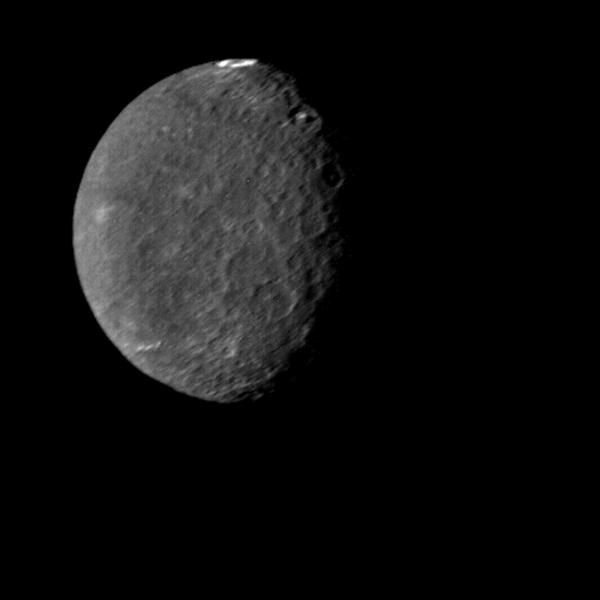 The southern hemisphere of Umbriel displays heavy cratering in this NASA Voyager 2 image, taken Jan. 24, 1986. This frame is the most detailed image of Umbriel, the darkest of Uranus' larger moons.