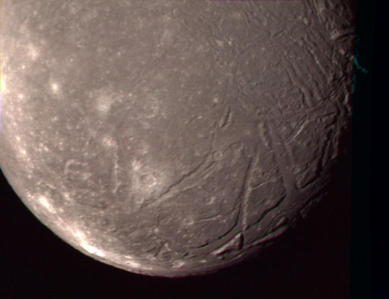 On Jan. 24, 1986, NASA's Voyager 2 obtained this color picture of the Uranian moon, Ariel. Most of the visible surface consists of relatively intensely cratered terrain transected by fault scarps and fault-bounded valleys (graben).